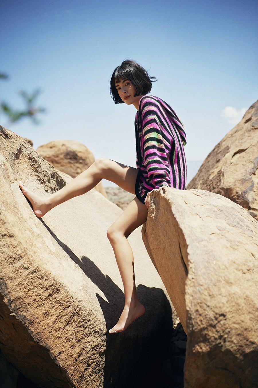 写真は、岩に腰掛ける大屋夏南さん