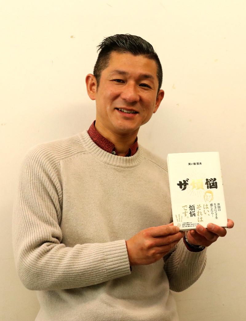 『ザ煩悩』(KADOKAWA)を持つ笑い飯の哲夫さん
