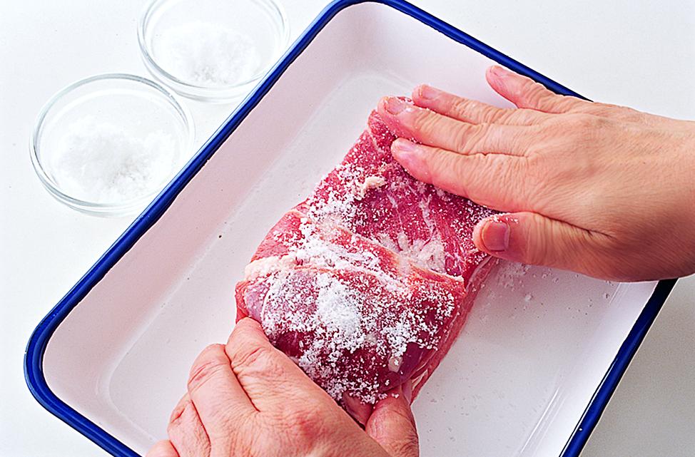 写真は、豚かたまり肉に塩をもみ込む様子/『ちょこっと仕込みで即ウマごはん』(主婦の友社)より