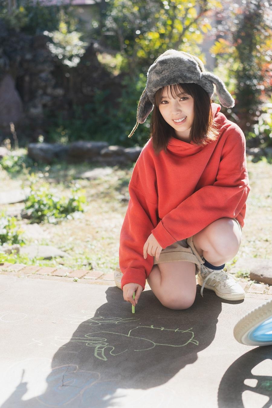 写真は、地面に落書きをする与田祐希さん(提供:東京ニュース通信社)