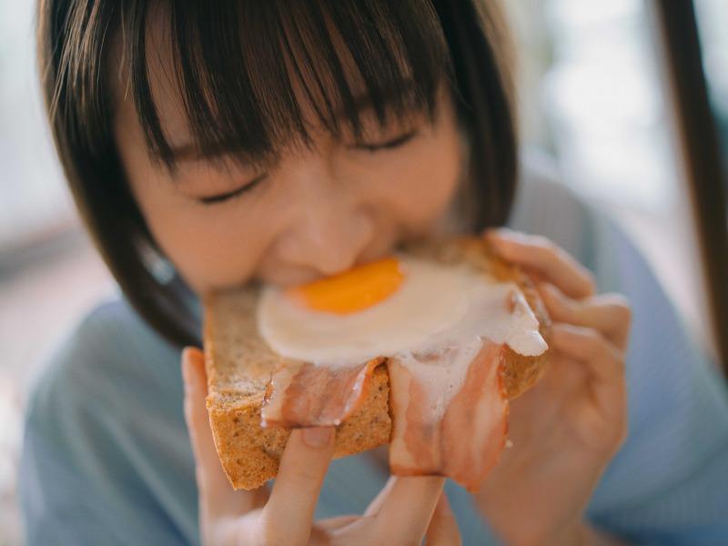 写真は、目玉焼きトーストにかじりつく岡崎紗絵さん(提供:主婦の友社)